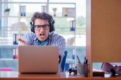 El adicto al videojugador que juega a los juegos de ordenador en casa imagen de archivo