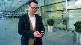 El administrador de oficinas de sexo masculino está caminando a lo largo del edificio y del funcionamiento un smartphone con una