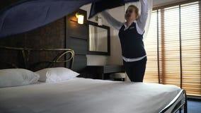 El administrador sonriente corrige las ropas de cama en el cuarto moderno del hotel Cámara lenta metrajes