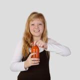 El adolescente abre una botella de jugo de zanahoria Fotografía de archivo