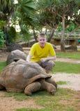 El adolescente acaricia a una tortuga Fotografía de archivo