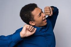 El adolescente afroamericano cansado se está estirando foto de archivo