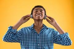 El adolescente afroamericano en auriculares escucha la música Imagen de archivo