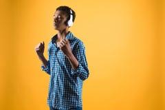 El adolescente afroamericano en auriculares escucha la música Foto de archivo