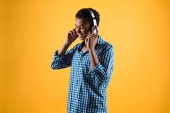 El adolescente afroamericano en auriculares escucha la música Foto de archivo libre de regalías