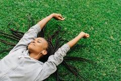 El adolescente afroamericano encantado está disfrutando de música mientras que pone en la hierba y aumenta las manos Foto de archivo libre de regalías