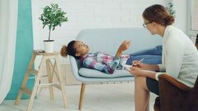 El adolescente afroamericano está hablando con el psicólogo que miente en el sofá y que sonríe mientras que el terapeuta está esc almacen de metraje de vídeo