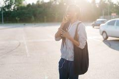 El adolescente afroamericano feliz está hablando vía el sellphone durante la puesta del sol El retrato al aire libre Fotos de archivo