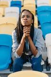 El adolescente afroamericano hermoso está observando el partido en el estadio Imagen de archivo