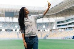 El adolescente afroamericano pensativo beauitful está tomando el selfie vía el teléfono móvil en el estadio Foto de archivo