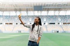 El adolescente afroamericano sonriente está tomando el selfie en el fondo del estadio Imagenes de archivo