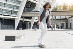 El adolescente alegre está montando en la calle con placer Foto de archivo libre de regalías