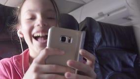 El adolescente alegre juega a un juego en smartphone en la cabina del avión mientras que vídeo común de la cantidad que viaja metrajes