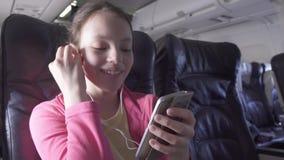 El adolescente alegre juega a un juego en smartphone en la cabina del avión mientras que vídeo común de la cantidad que viaja almacen de video
