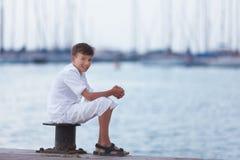 El adolescente alegre mira la nave el mar y los sueños Foto de archivo libre de regalías