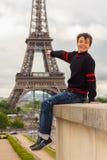 El adolescente alegre muestra la torre Eiffel, Francia Fotografía de archivo libre de regalías