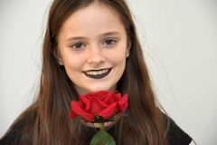 El adolescente amistoso con negro pintó los labios y la rosa del rojo Imagen de archivo