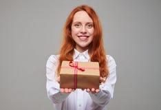 El adolescente apuesto del pelirrojo ofrece una caja de regalo Fotos de archivo