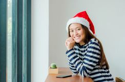 El adolescente asiático con el sombrero de la Navidad y la sonrisa hacen frente a descansarla Imagen de archivo