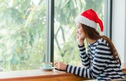 El adolescente asiático con el sombrero de la Navidad y la sonrisa hacen frente a descansarla Fotografía de archivo