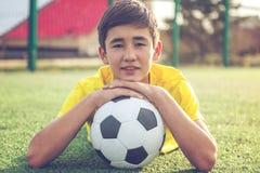 El adolescente asiático del muchacho con una bola del fútbol miente en la hierba Deporte Fotografía de archivo libre de regalías