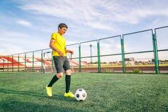 El adolescente asiático en un campo de fútbol con una bola, deportes y entra Fotografía de archivo libre de regalías
