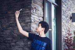 El adolescente asiático que usa el teléfono móvil toma el selfie de la foto Foto de archivo libre de regalías