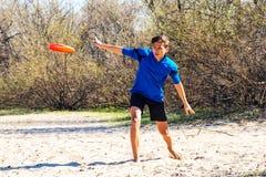 El adolescente atlético está lanzando entusiasta el disco del disco volador Imágenes de archivo libres de regalías