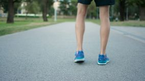 El adolescente atlético que comienza a correr lejos de cámara, joggin corriente calza el primer almacen de metraje de vídeo