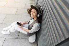El adolescente atractivo positivo está descansando sobre la calle Foto de archivo