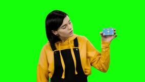 El adolescente aumenta una tarjeta de banco y muestra los pulgares para arriba Pantalla verde almacen de video