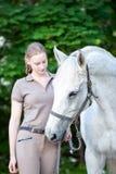 El adolescente bastante joven lleva el caballo blanco Foto de archivo libre de regalías