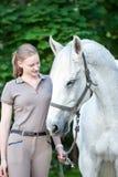 El adolescente bastante joven lleva el caballo blanco Fotografía de archivo