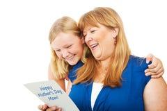 Adolescente da la tarjeta del día de madres a la mamá Fotografía de archivo