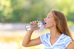 El adolescente bebe el agua de Foto de archivo