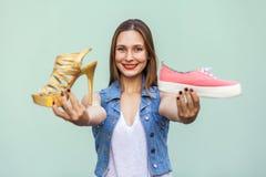 El adolescente blando y lindo con las pecas consiguió que elegía en las zapatillas de deporte de la tienda o los zapatos incómodo Imagen de archivo