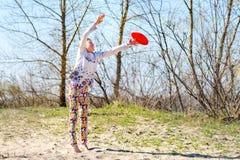 El adolescente, blonde coge el disco del vuelo en un salto Fotografía de archivo libre de regalías