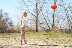 El adolescente, blonde está lanzando el disco y la sonrisa del vuelo Imagen de archivo