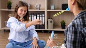 El adolescente bonito está jugando con las burbujas de jabón almacen de video