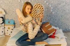 El adolescente bonito está sosteniendo las almohadas con las letras de amor mientras que se sienta en el sofá Fotos de archivo libres de regalías