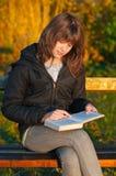 El adolescente bonito lee el libro en el parque Imagen de archivo