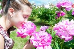 El adolescente bonito que huele la peonía floreciente rosada florece en el PA Fotos de archivo