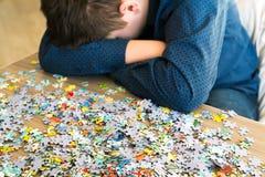 El adolescente cansado se está sentando inclinando su cabeza al lado de rompecabezas Imagen de archivo