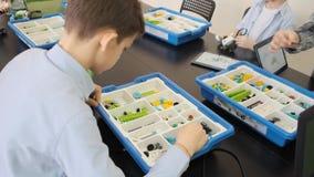El adolescente caucásico construye su helicóptero plástico usando los detalles de la caja en la cámara lenta de la lección que di metrajes