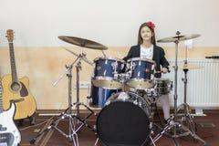el adolescente caucásico joven juega los tambores muchacha que juega el sistema del tambor Fotos de archivo libres de regalías
