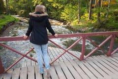 El adolescente caucásico se coloca en el puente de madera Imagen de archivo