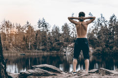 El adolescente cerca del lago se sienta en una roca Imagen de archivo
