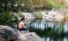 El adolescente cerca del lago se sienta en una roca Fotografía de archivo libre de regalías