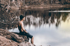 El adolescente cerca del lago se sienta en una roca Imagenes de archivo