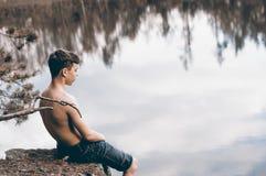 El adolescente cerca del lago se sienta en una roca Foto de archivo